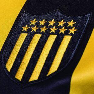 Lo stemma del Peñarol: le strisce gialle e oro indicano la ferrovia e i colori del CURCC, le undici stelle simboleggiano i giocatori.