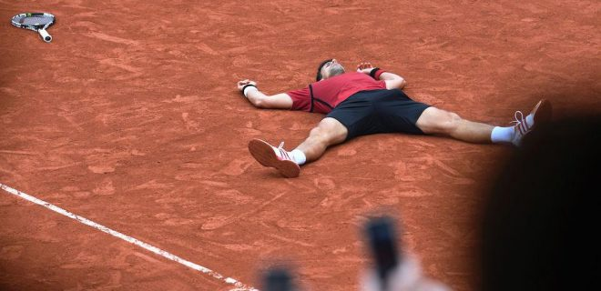 Serbia's Novak Djokovic lies on the court as he reacts after winning his men's final match against Britain's Andy Murray at the Roland Garros 2016 French Tennis Open in Paris on June 5, 2016. / AFP / MIGUEL MEDINA        (Photo credit should read MIGUEL MEDINA/AFP/Getty Images)